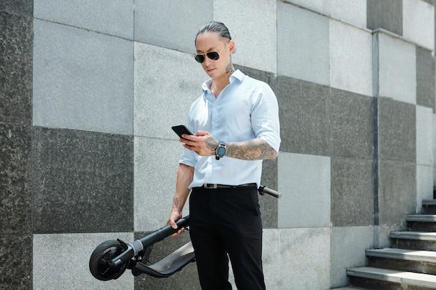 Grave giovane uomo d'affari accigliato in bicchieri tenendo scooter e rispondere a messaggi di testo da colleghi e clienti