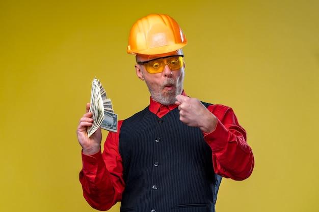 Appaltatore generale serio o concetto di investitore immobiliare con uomo elegante con barba, occhiali e casco da costruzione. uomo in camicia elegante. soldi in mano.