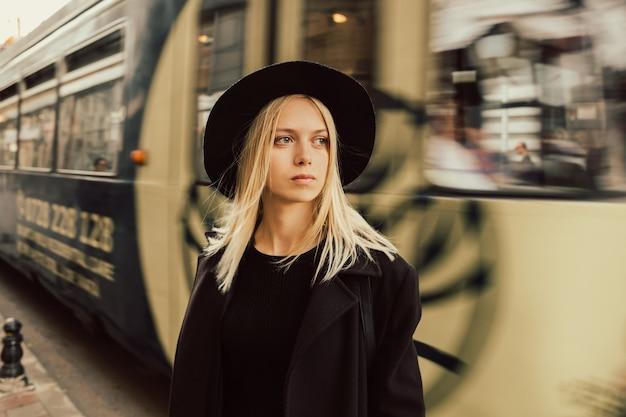 Ragazza seria in cappello nero alla stazione ferroviaria.