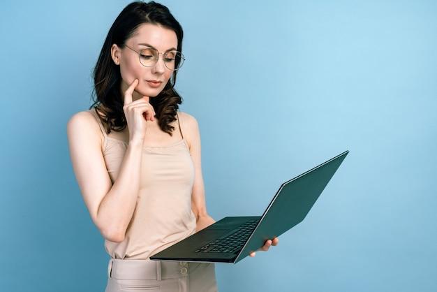 La ragazza seria sta lavorando su un laptop, pensando e analizzando qualcosa.
