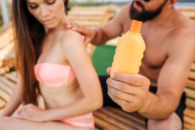 Ragazzo e ragazza seri siedono. mette un po 'di crema solare dalla bottiglia arancione sulle spalle e sulla schiena. lei guarda in basso.
