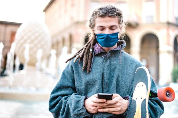 Ragazzo serio con maschera protettiva utilizzando l'app di monitoraggio sullo smartphone mobile