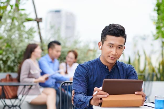 Uomo d'affari asiatico bello serio che si siede al tavolo in un caffè all'aperto e guardare la presentazione sulla tavoletta digitale