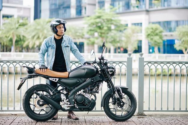 Uomo asiatico bello serio in casco che sta accanto alla sua moto sulla riva del fiume e distoglie lo sguardo