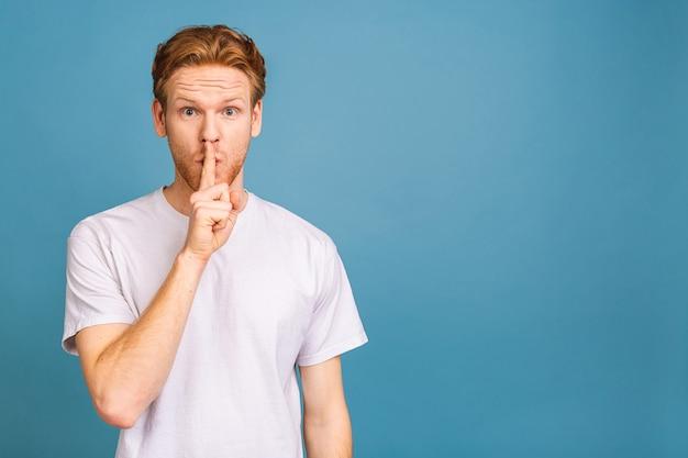 Un bell'uomo serio tiene il dito anteriore sulle labbra, cerca di mantenere la cospirazione