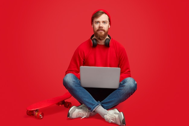Uomo serio hipster con laptop e skateboard