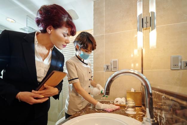 Direttore serio dell'hotel che controlla la cameriera in guanti e il bancone del bagno per la pulizia della maschera medica con spray disinfettante