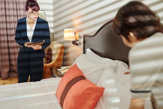 Direttore d'albergo serio con tablet digitale che guarda la nuova cameriera che fa il letto e aggiusta i cuscini morbidi