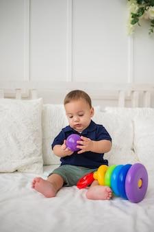 Il ragazzo serio del bambino raccoglie il giocattolo della piramide sul letto bianco