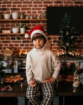 Un ragazzino serio è seduto sul tavolo della cucina con un maglione bianco e un cappello rosso di natale