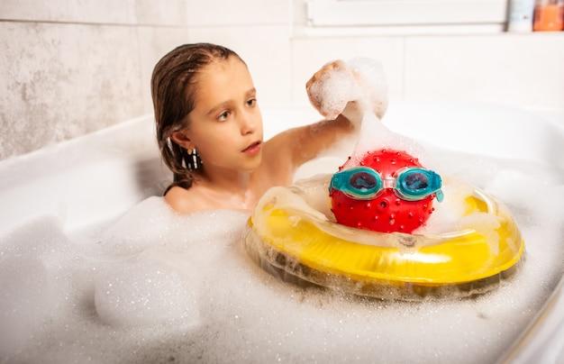 Una ragazzina seria e carina si bagna in un bagno di schiuma e gioca con i giocattoli immaginandosi al mare. concetto di sogno per bambini di una vacanza estiva al mare
