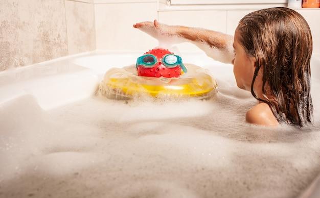 Serious little girl cute fa il bagno in un bagno di schiuma e gioca con i giocattoli immaginando se stessa al mare