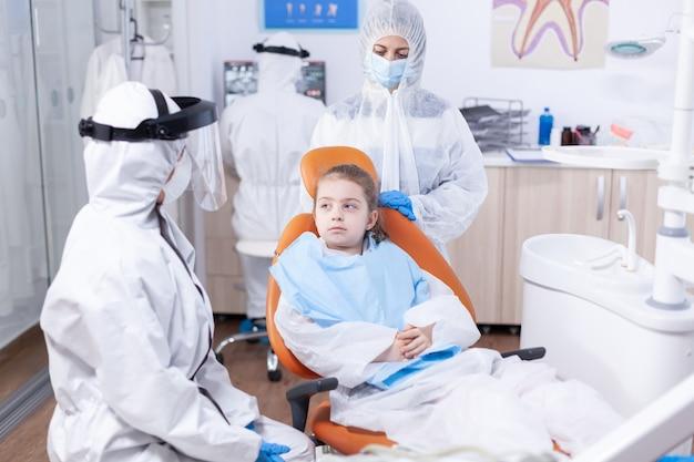 Grave bambina seduta in poltrona odontoiatrica ascolto dentista parlando del trattamento per la cavità. stomatologo durante il covid19 che indossa una tuta in dpi facendo la procedura dei denti del bambino seduto sulla sedia.