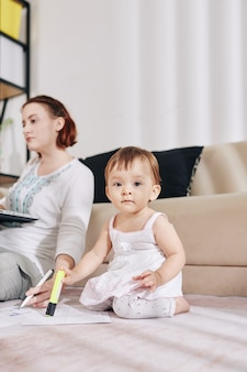 Bambina seria che si siede sul pavimento e disegna con l'evidenziatore sui documenti di sua madre