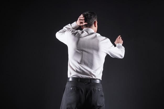 Sguardo serio. intelligente bell'uomo premuroso tenendo la testa e guardando lo schermo sensoriale mentre pensa al suo problema