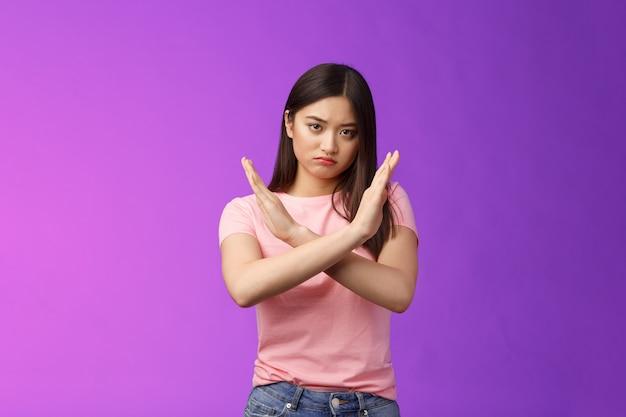 Una ragazza asiatica infastidita dall'aspetto serio chiede di fermarsi, fa un gesto proibito con il braccio incrociato sul petto, guarda con disprezzo e delusione, rifiuta un'offerta terribile, dà il rifiuto, vuole porre fine alla discussione.