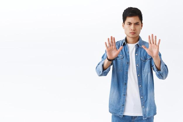 L'uomo asiatico dall'aspetto serio richiede di mantenere le distanze durante il virus covid-19, alzare le mani e accigliato il giudizio, sembrando un'azione di disapprovazione molto seria, muro bianco