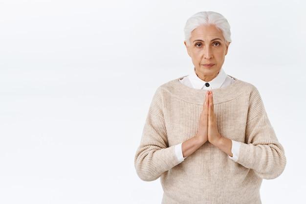 Anziana determinata e paziente dall'aspetto serio, signora anziana con i capelli grigi pettinati, premere i palmi insieme sul petto in gesto di supplica, pregare, implorare qualcuno, stare in piedi sul muro bianco