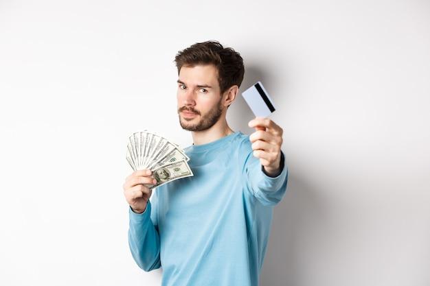 Un ragazzo dall'aspetto serio allunga la mano con una carta di credito in plastica, preferisce il pagamento senza contatto invece che in contanti, in piedi su sfondo bianco.