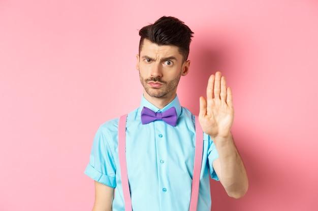 Un uomo dall'aspetto serio proibisce qualcosa di brutto, allunga la mano per fermarti, proibisce l'azione, dice di no e sembra severo, in piedi sul rosa.