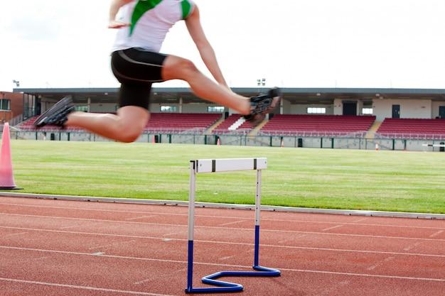 Atleta maschio serio che salta sopra la barriera durante la corsa