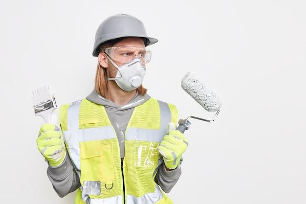 Il decoratore maschio serio offre un servizio professionale tiene la spazzola a rullo per pittura utilizza strumenti