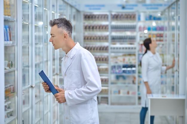 Drogatore maschio serio con una lavagna per appunti e la sua collega che ispezionano l'area di stoccaggio dei farmaci