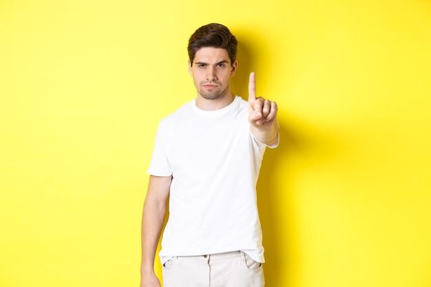 Uomo serio che aggrotta la fronte dispiaciuto, scuote un dito per proibire qualcosa, ti avverte, in piedi sopra il muro giallo