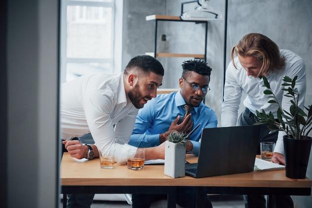 Uomo serio completamente concentrato. uomini d'affari multirazziali con laptop che risolvono i problemi dell'azienda