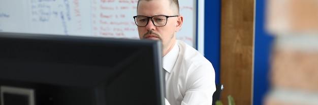 L'uomo serio con gli occhiali e la camicia si siede e guarda il monitor del computer. sullo sfondo c'è una lavagna bianca con testo.