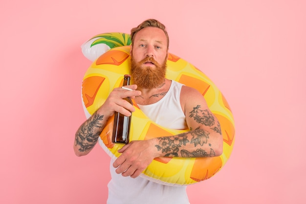 L'uomo serio è pronto a nuotare con un salvagente a ciambella con birra e sigaretta in mano