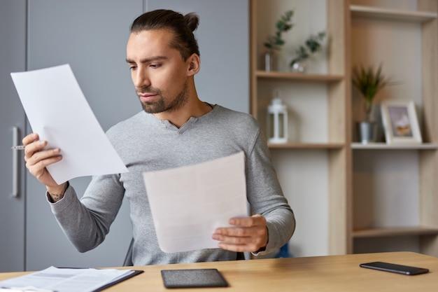 Uomo serio che legge documenti finanziari a casa