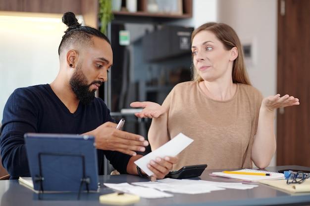 Uomo serio che mostra il conto non pagato alla moglie confusa quando discutono del budget familiare