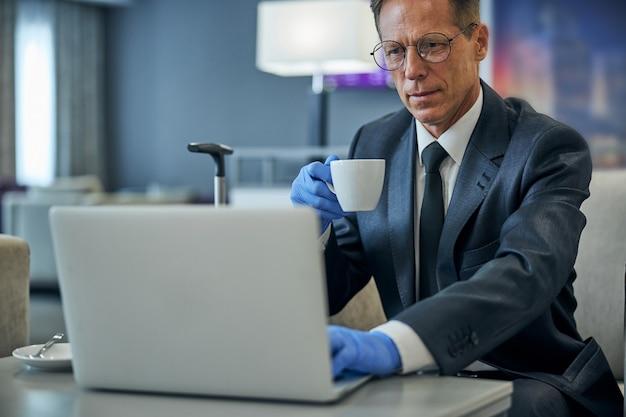 Uomo serio in giacca e occhiali che beve caffè e usa il taccuino prima del volo durante la pandemia