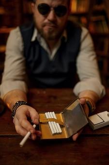 L'uomo serio in occhiali da sole tiene il portasigarette, la libreria e l'interno dell'ufficio ricco sullo sfondo. cultura del fumo di tabacco, sapore specifico. abitudine al fumo