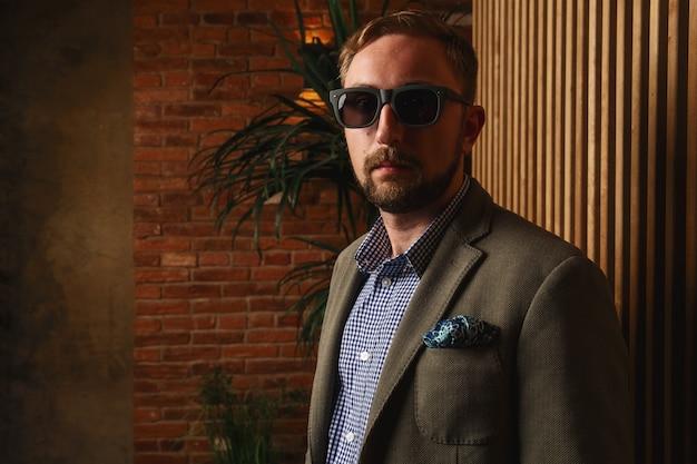 Uomo serio in occhiali da sole e giacca verde moderna in piedi vicino al muro di legno in appartamento loft