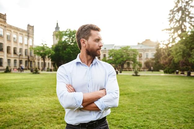 Uomo serio in camicia bianca, guardando da parte durante una passeggiata nel parco verde, mentre in piedi con le braccia conserte sul vecchio edificio
