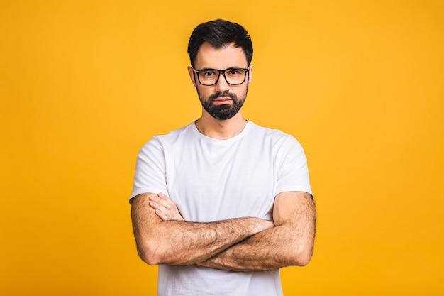 Uomo serio con le mani incrociate piegate in piedi isolato su sfondo giallo e che guarda l'obbiettivo