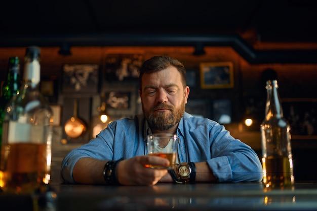 Uomo serio con un bicchiere di alcol seduto al bancone del bar. una persona di sesso maschile che riposa in un pub, emozioni umane, attività ricreative, vita notturna