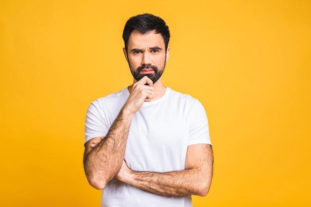 Uomo serio con le mani giunte in piedi isolato su sfondo giallo e che guarda l'obbiettivo