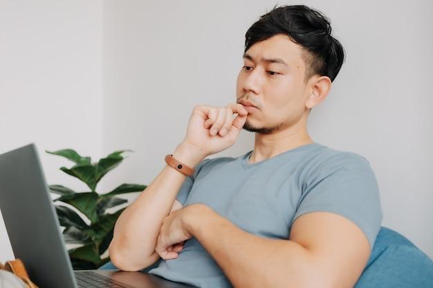 L'uomo serio lavora al computer portatile mentre resta a casa