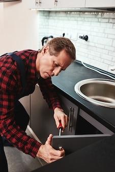Serio maestro anziano tuttofare che ripara mobile da cucina