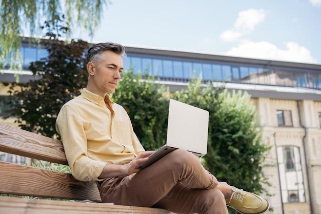 Grave imprenditore maturo utilizzando laptop, lavorando nel parco, seduto su una panchina