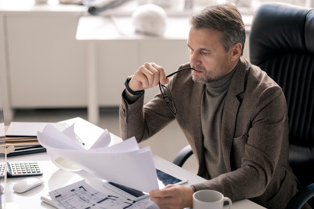 Direttore maturo serio dell'azienda o ingegnere con gli occhiali seduto alla scrivania e guardando attraverso i documenti con schizzi