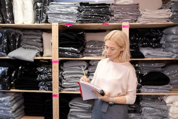 Assistente di negozio maturo serio che prende appunti in un grande quaderno mentre lavora nel ripostiglio contro gli scaffali con i vestiti imballati