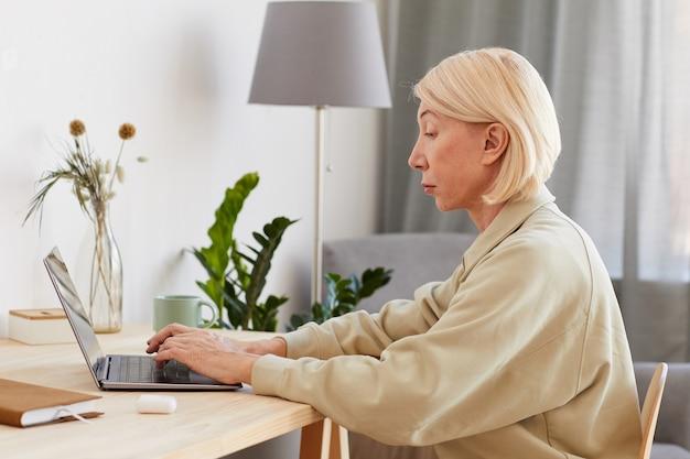 Donna matura seria che si concentra sul suo lavoro in linea sul computer portatile al tavolo a casa