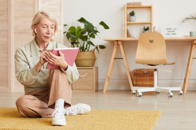 Grave donna matura seduta sul pavimento e lavora online su tavoletta digitale a casa