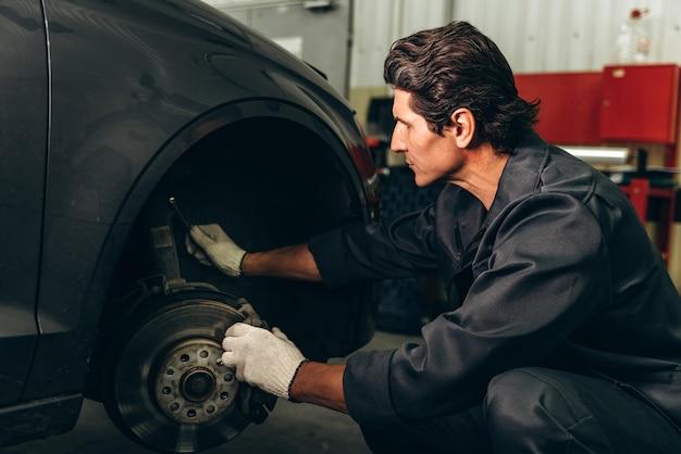 Meccanico serio che indossa guanti che si preparano a posizionare una ruota in un'auto. checkup auto e concetto di servizio auto. foto d'archivio