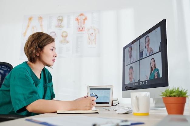 Operaio medico serio che ha riunioni online con i colleghi e discute di innovazioni