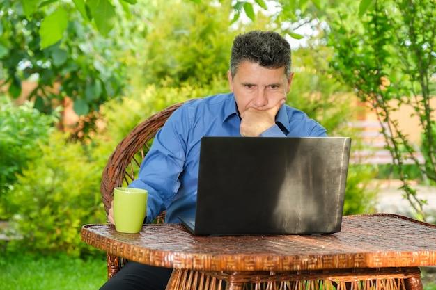 Grave uomo d'affari di mezza età che beve caffè e legge notizie usando il portatile seduto nel suo giardino sul retro. concetto di lavoro a distanza